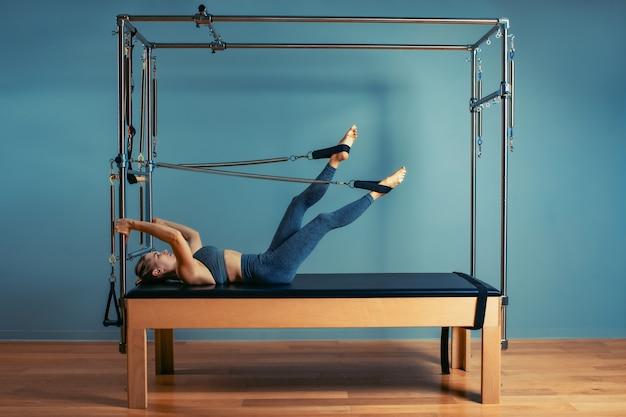 改質ベッドでピラティス運動をしている若い女の子。改質装置の灰色の背景、低キー、アートライトの美しいスリムフィットネストレーナー。フィットネスの概念