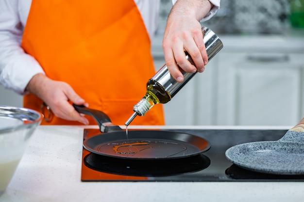 キッチンの準備:シェフがフライパンに油を注ぐ