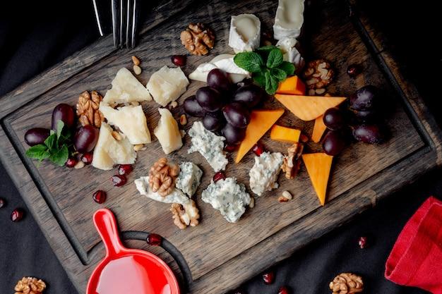 チーズプレートは、ブドウ、蜂蜜、木製の背景上のナッツを添えてください。各種チーズ