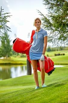 目標のコンセプト、コピースペース。グリーンフィールドスペースでゴルフ用品を保持している女性のゴルフの時間。卓越性、個人の職人技、ロイヤルスポーツ、スポーツバナーの追求。