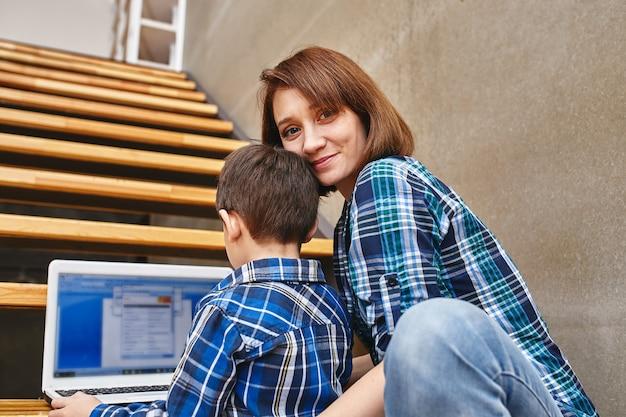 Мама и сын делают домашнее задание на компьютере. концепция мамы и детей, современные технологии и интернет.
