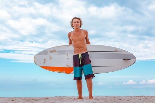 Прогулка красивого человека с белой пустой доской для серфинга для волны для серфинга берега океана пятна на море. концепция спорта, фитнеса, свободы, счастья, новой современной жизни, битник.