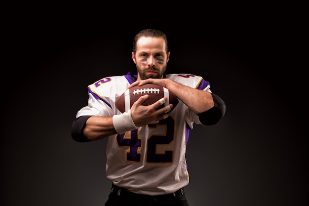 試合前に祈る瞬間にボールを持つアメリカンフットボール選手