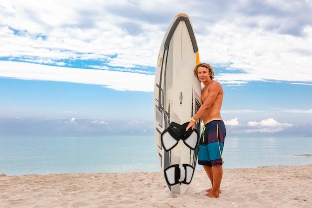 ハンサムな男は白い空白のサーフィンボードで歩く海波海岸でスポットをサーフィンする波を待ちます。スポーツ、フィットネス、自由、幸福、新しい現代生活、ヒップスターの概念。