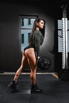 ジムでバーベルをスクワットし、脚の筋肉を発達させ、脊椎を強化します。健康な体、フィットネスの動機