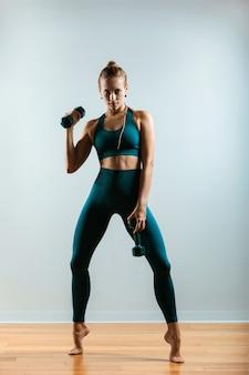 Красивая фитнес-модель делает упражнения с гантелями в руках. девушка занимается спортом в тренажерном зале на сером фоне.