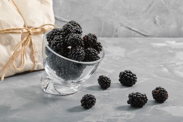 Ежевика на черном фоне, крупным планом, свежие ягоды в миску на бетонном фоне с завернутый конверт с ягодой.