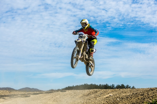 Гонщик на мотоцикле в полете, прыгает и взлетает на трамплине на фоне неба.