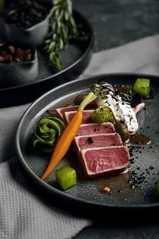 Тальята из тунца с овощами, тушеной морковью и перцем, красивая сервировка, традиционная итальянская кухня