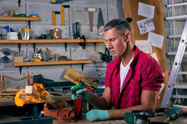 プロのガスバーナーで木製の足を燃やす専門家の大工。炎と煙、火と木材。キャビネットの肖像