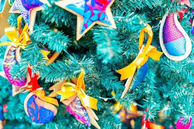 お祭りの背景の上のクリスマスツリーの装飾へのクローズアップ