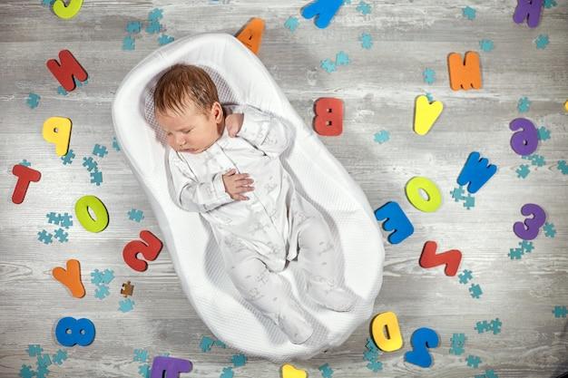 生まれたばかりの赤ちゃんは特別な整形外科マットレスで眠る赤ちゃんの繭