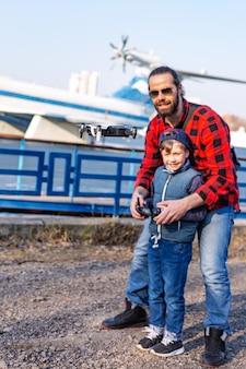 Отец и сын держат пульт дистанционного управления джойстиком и пилотируют квадрокоптер