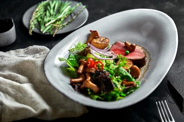 野菜と牛肉のタリアータ。クローズアップ、低キー、グレー。