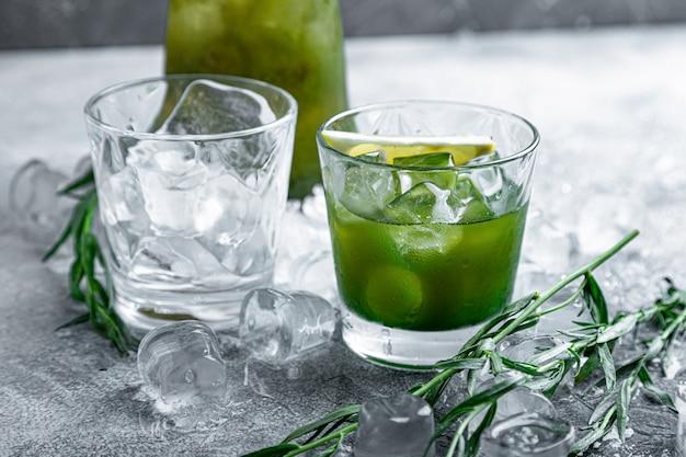 Эстрагон лимонад. освежающие летние напитки. свежий прохладный лимонад эстрагон с кусочками льда и цитрусовых.