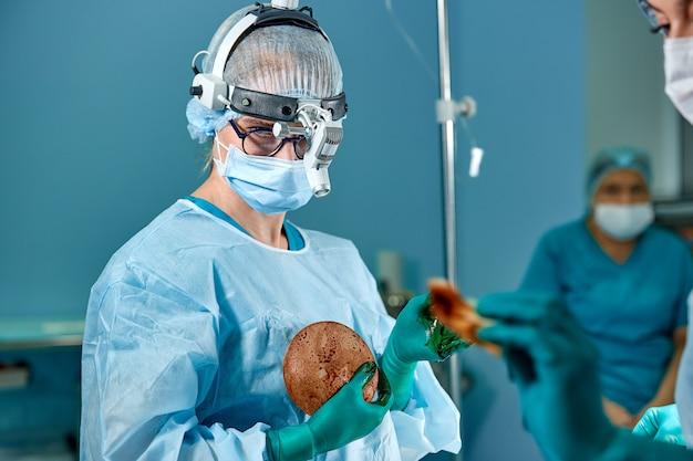手術のための乳房シリコーンインプラントを準備する外科医