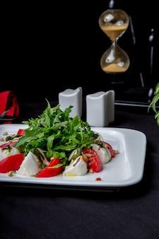 黒いテーブルにモッツァレラチーズとトマトの地中海サラダ