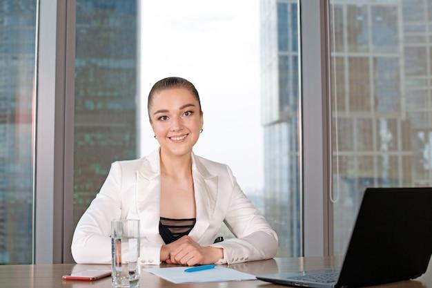 窓の近くに座ってラップトップに取り組んで自信を持って若い女性