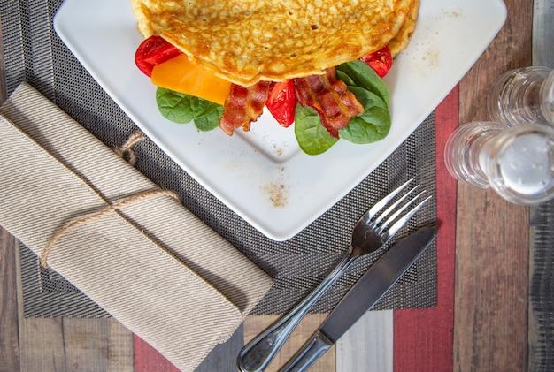 チーズ、グリルトマト、ハム、サクサクしたベーコン、サラダのオムレツをおいしいクローズアップ