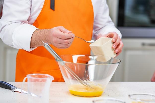 シェフが溶いた卵に砂糖を加えます