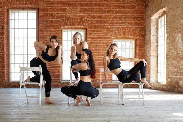 Группа молодых спортивных девушек отдыхает после тренировки в просторной лофте студии.