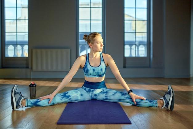 柔軟性を維持します。床に座ってストレッチを行うスポーツウェアの若い美しい女性