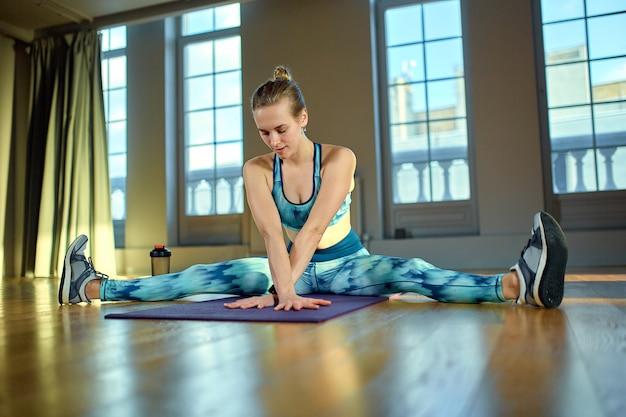 柔軟性を維持します。ジムの窓の前の床に座ってストレッチを行うスポーツウェアの若い美しい女性