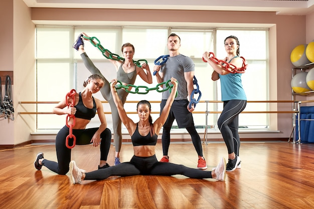 スポーツウェア、フィットネスルーム、ジムで腕立て伏せや板をしているスポーツ若者のグループ。