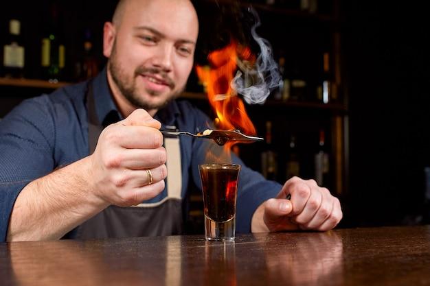 バーでの燃えるようなショー。バーテンダーは熱いアルコールカクテルを作り、バーに火をつけます。バーテンダーは燃えるようなカクテルを準備します。バーで発射します。