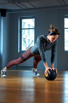 Красивая подходит женщина в спортивной одежде позирует сидя на полу с баскетболом перед окном в тренажерном зале здоровый образ жизни девушки и спорт