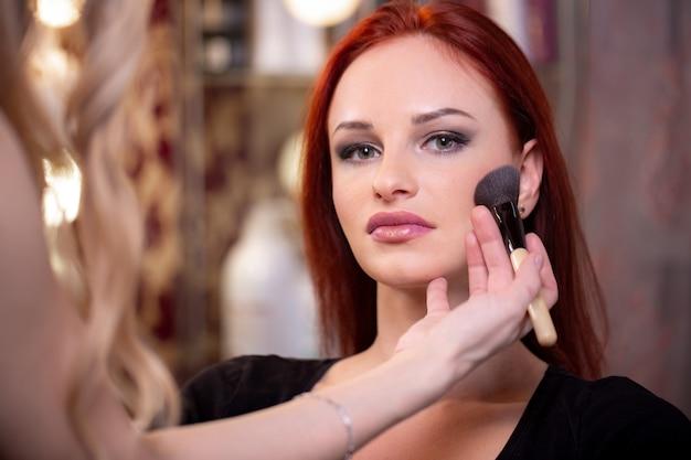 白いメイクアップルームで女性の顔にリキッドトーンファンデーションを適用するメイクアップアーティスト。