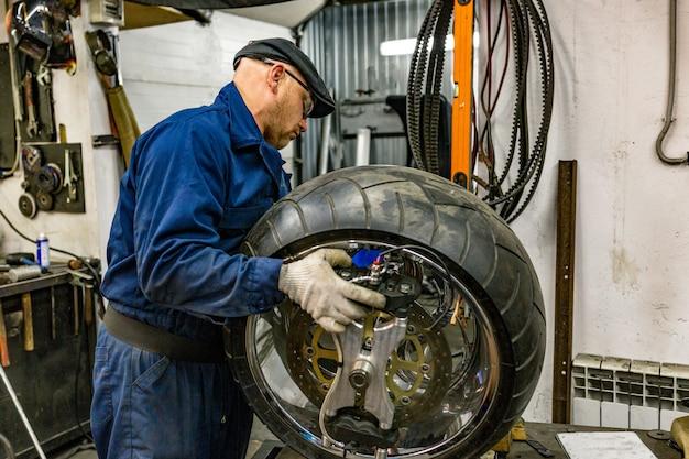 修理キット、チューブレスタイヤのタイヤプラグ修理キットでバイクのタイヤを修理する男。