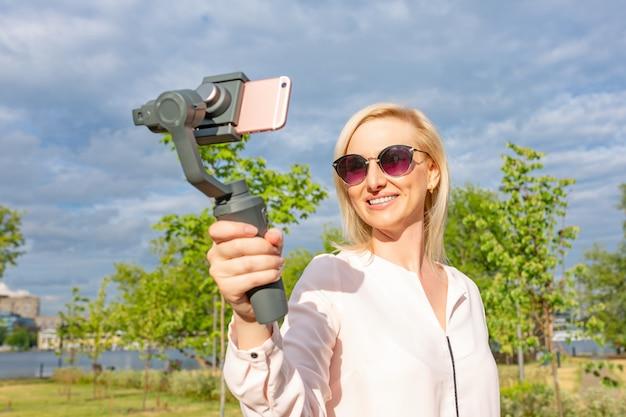 スタビライザーを携帯している女の子がビデオブログをリードしています。彼女はカメラのスマートフォンに身を任せる