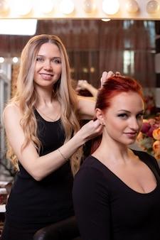 Красивая, рыжеволосая девушка с длинными волосами, парикмахер плетет французскую косу, в салоне красоты. профессиональный уход за волосами и создание причесок.