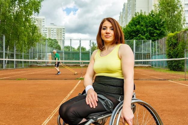 テニスコートでテニスをしている車椅子の若い女性を無効に。