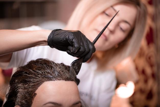Окрашивание волос в салоне, укладка волос. профессиональный мастер красит волосы в салоне. концепция красоты, уход за волосами.
