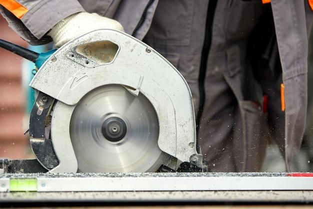 ワーム駆動のハンドヘルド丸鋸を使用してボードとプラスチックを切断する建設請負業者の労働者。建設、独自のワークショップ、木材を切断する作業契約を雇います。
