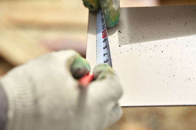 Плотницкие работы с использованием рулетки для измерения деревянной доски и маркировки ее карандашом.
