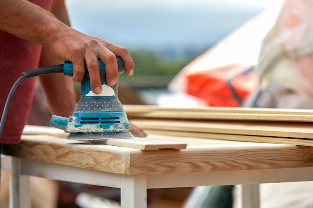 グラインダーワーカーは木の板を磨きます。サンディングボードオービタルエキセントリックマシン。