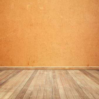 オレンジ色の壁の背景に木製の床