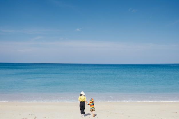母と息子の手を握って夕暮れ時の屋外のビーチと海の上を歩く