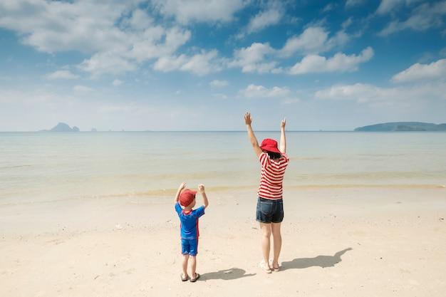Мать и сын на пляже на открытом воздухе море и голубое небо