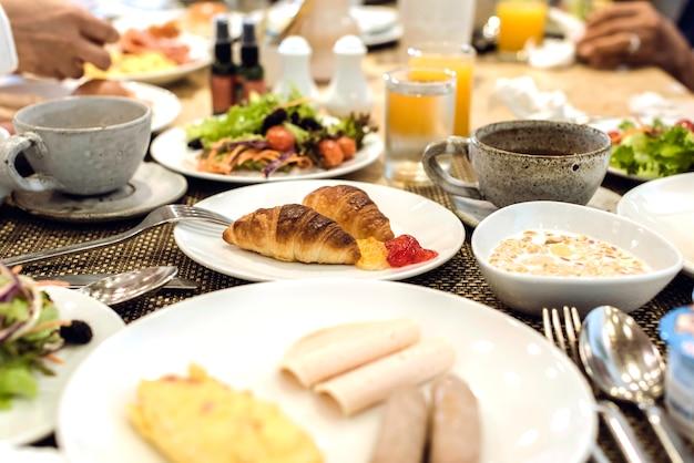Круассаны - это ингредиент завтрака. завтрак на столе с кофе, апельсиновым соком, фруктами, салатом, яйцом, беконом, круассанами, мармеладом, молоком и водой.
