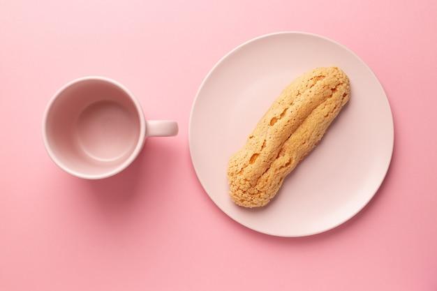 プレート上のエクレア。ピンクのパステル背景。デザート。コンセプト、ミニマリズム