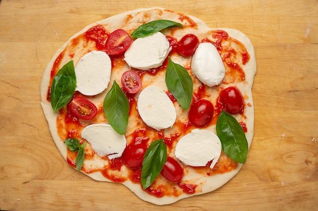 Сырая домашняя пицца на разделочной доске сверху