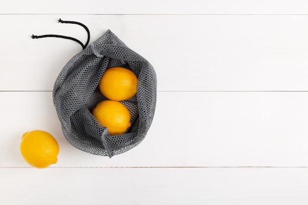 白い背景の上のレモンと再利用可能なショッピングバッグ