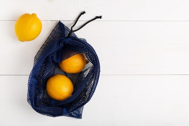 Многоразовая сумка с лимонами на белом фоне