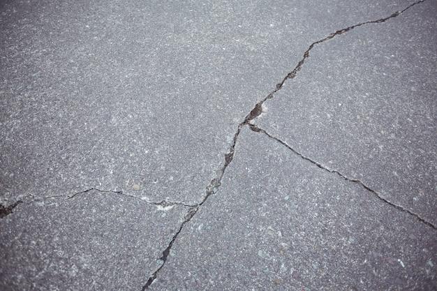 割れたアスファルト道路背景のクローズアップ