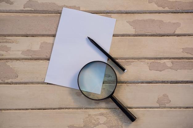 虫眼鏡と鉛筆で白紙
