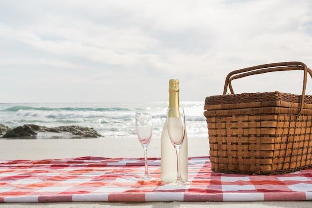 Два бокала, бутылка шампанского и корзина для пикника на пляже одеяло